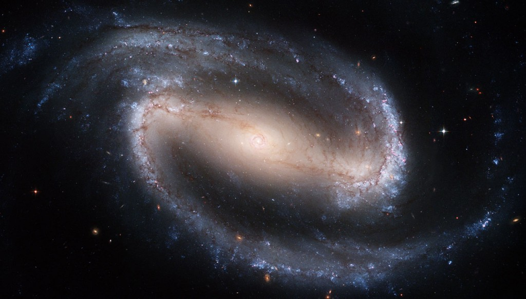 The Hubble telescope captured a display of starlight, glowing gas, and silhouetted dark clouds of interstellar dust in this 4-foot-by-8-foot image of the barred spiral galaxy NGC 1300. NGC 1300 is considered to be prototypical of barred spiral galaxies. Barred spirals differ from normal spiral galaxies in that the arms of the galaxy do not spiral all the way into the center, but are connected to the two ends of a straight bar of stars containing the nucleus at its center.